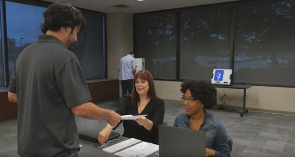 Poll worker handing voter a paper ballot