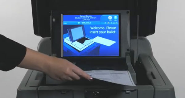 Voter feeding their ballot into the scanner