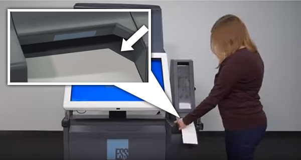 Voter inserting ballot paper into machine.