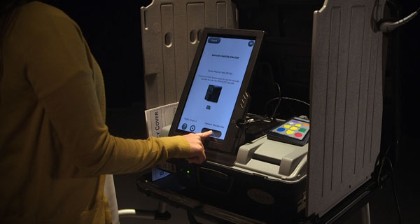 Voter touching the Start button on the Unisyn OpenElect ballot marking device with privacy screen.