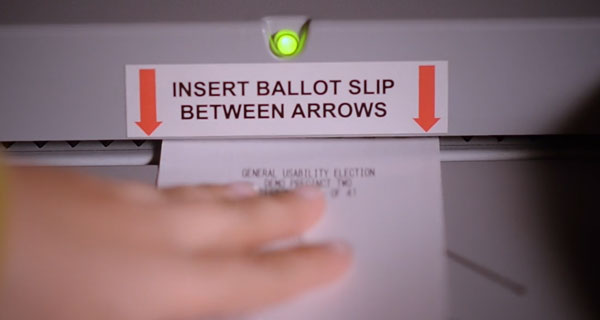 Paper ballot being inserted into the scanner between the arrows with a green light.